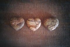 Tres corazones de piedra en la madera Fotografía de archivo