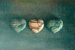 Tres corazones de piedra en la madera Fotos de archivo