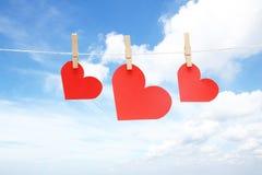 Tres corazones en clavijas de madera Fotos de archivo