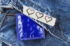 Tres corazones representados en el papel y el condón rasgados en paquete azul de la hoja en vaqueros Imágenes de archivo libres de regalías