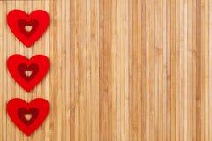 Tres corazones rojos en un fondo de madera, un día del ` s de la tarjeta del día de San Valentín del fuerte de la tarjeta fotografía de archivo