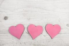 Tres corazones rosados en viejo fondo elegante lamentable blanco de madera Fotografía de archivo