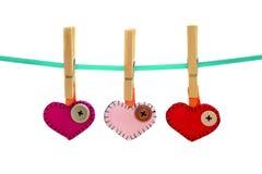 Tres corazones y clavijas imagenes de archivo