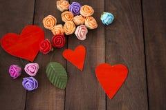 Tres corazones y flores rojos en una madera marrón del fondo Imagenes de archivo