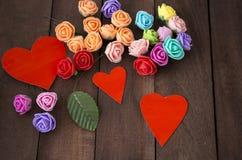 Tres corazones y flores rojos en una madera marrón del fondo Imágenes de archivo libres de regalías