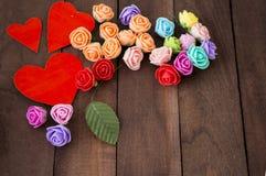 Tres corazones y flores rojos en una madera marrón del fondo Fotografía de archivo libre de regalías