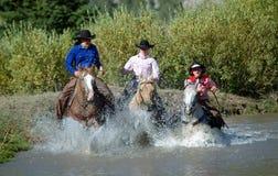 Tres Cowgirls que entran en la charca Foto de archivo libre de regalías
