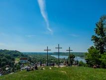 Tres cruces cristianas en la colina con el en de la gente Imagen de archivo libre de regalías