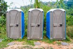 Tres cuartos de retrete móvil plástico público en bosque Imagen de archivo libre de regalías