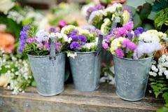 Tres cubos de flores púrpuras y blancas hermosas se prepararon para la ceremonia de boda Fotografía de archivo libre de regalías