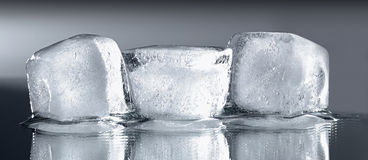 Tres cubos de hielo con la reflexión Foto de archivo