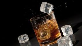 Tres cubos de hielo que caen en el vaso del whisky y del hielo almacen de metraje de vídeo