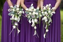 Tres damas de honor que sostienen ramos de la boda Foto de archivo libre de regalías