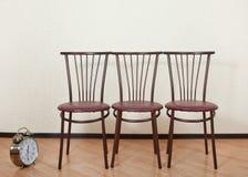 Tres de la misma silla contra la pared Imagen de archivo