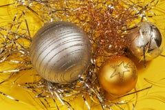 Tres de plata y bola decorativa de oro de la Navidad en el hilo metálico en fondo amarillo Fotos de archivo libres de regalías