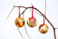 Tres decoraciones de la Navidad en una rama seca Imagen de archivo libre de regalías