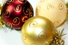 Tres decoraciones multicoloras de la Navidad en la forma de un globo, pintado con los modelos del oro Imágenes de archivo libres de regalías