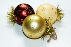 Tres decoraciones multicoloras de la Navidad en la forma de un globo, pintado con los modelos del oro Imagenes de archivo