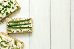 Tres desayunos dietéticos con requesón e hierbas en una tabla de madera blanca, espacio para el texto foto de archivo libre de regalías