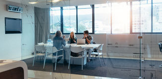 Tres diseñadores que discuten en pasillo de reunión Fotos de archivo