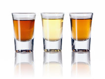 Tres clases de bebidas alcohólicas en vasos de medida Fotografía de archivo libre de regalías