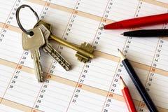 Tres diversas llaves en un calendario y una opinión superior de las plumas Fotografía de archivo