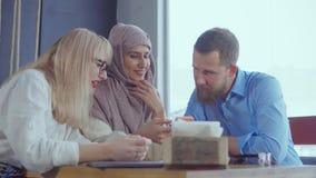 Tres diversos amigos étnicos hombre y mujeres están charlando en café en d3ia metrajes