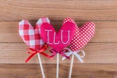 Tres diversos corazones de la tela en los palillos de madera con los arcos de la cinta puestos en un fondo de madera Día de tarje fotos de archivo libres de regalías