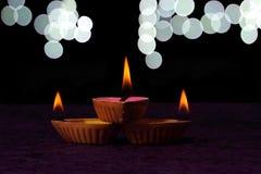Tres diyas y bokeh del diwali en fondo Imagenes de archivo