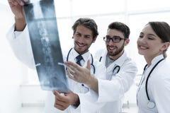 Tres doctores confiados examinan una radiografía Fotografía de archivo libre de regalías