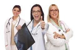 Tres doctores o enfermeras de sexo femenino con los pulgares que detienen la radiografía Fotografía de archivo libre de regalías