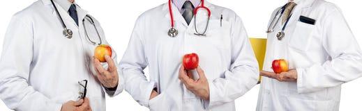 Tres doctores que llevan los estetoscopios que sostienen manzanas jugosas Imágenes de archivo libres de regalías