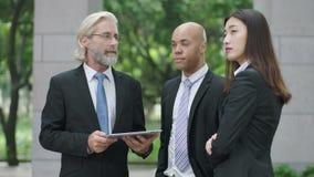 Tres ejecutivos empresariales que discuten negocio usando la tableta digital metrajes