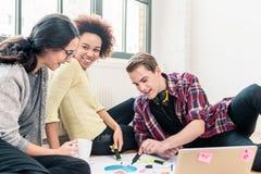 Tres empleados creativos jovenes que trabajan junto en un proyecto foto de archivo