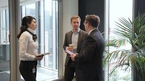 Tres empleados están hablando mientras que se colocan en pasillo de la compañía grande almacen de video
