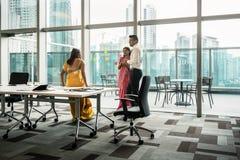 Tres empleados indios que hablan durante rotura en la sala de reunión imagenes de archivo