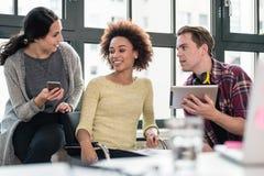 Tres empleados jovenes que usan los dispositivos modernos durante rotura fotos de archivo