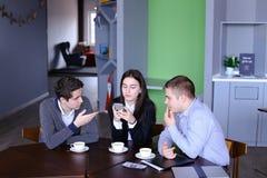 Tres empleados ocupados de la compañía, dos hombres jovenes y mujer ocupados con Imagen de archivo libre de regalías