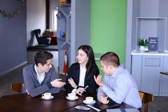 Tres empleados ocupados de la compañía, dos hombres jovenes y mujer ocupados con Fotos de archivo libres de regalías