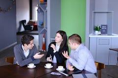 Tres empleados ocupados de la compañía, dos hombres jovenes y mujer ocupados con Foto de archivo libre de regalías