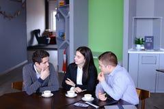 Tres empleados ocupados de la compañía, dos hombres jovenes y mujer ocupados con Foto de archivo