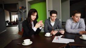 Tres empleados ocupados de la compañía, dos hombres jovenes y mujer ocupados con Imágenes de archivo libres de regalías