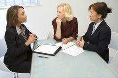 Tres empresarias en el escritorio Imagen de archivo libre de regalías