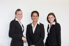 Tres empresarias jovenes multiétnicas attracttive en trajes de negocios negros imagen de archivo