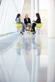 Tres empresarias que se encuentran alrededor del vector en oficina moderna Foto de archivo