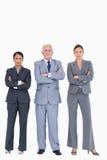 Tres empresarios con los brazos doblados Imágenes de archivo libres de regalías