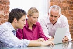 Tres empresarios en la oficina que mira la computadora portátil imágenes de archivo libres de regalías