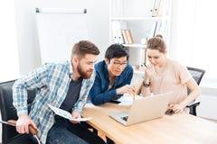 Tres empresarios enfocados que trabajan con el ordenador portátil en oficina imagenes de archivo