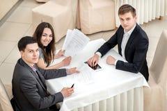 Tres empresarios jovenes que se sientan en una reunión Fotos de archivo libres de regalías