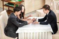 Tres empresarios jovenes que se sientan en una reunión Imágenes de archivo libres de regalías